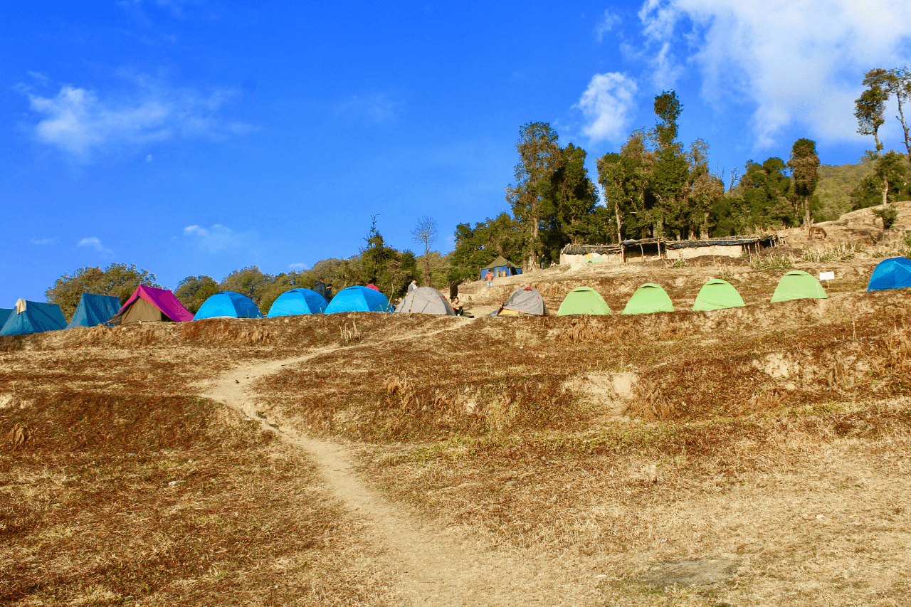 A row of tents perched on a hillock at Nag Tibba top.