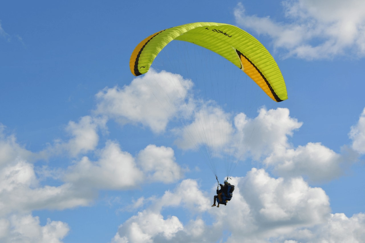 Tandem paragliders flying against blue sky with clouds.