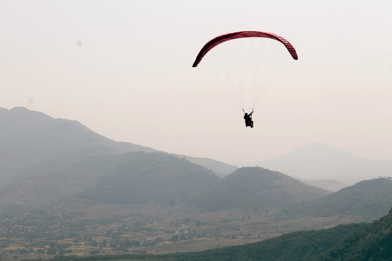 Paraglider soaring into the horizon with evening sky in background