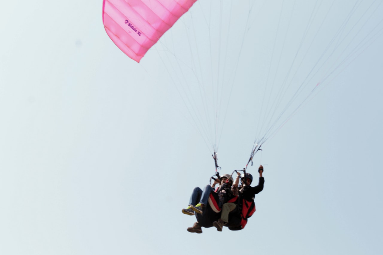 Tandem paragliding flight against a blue sky with white clouds.