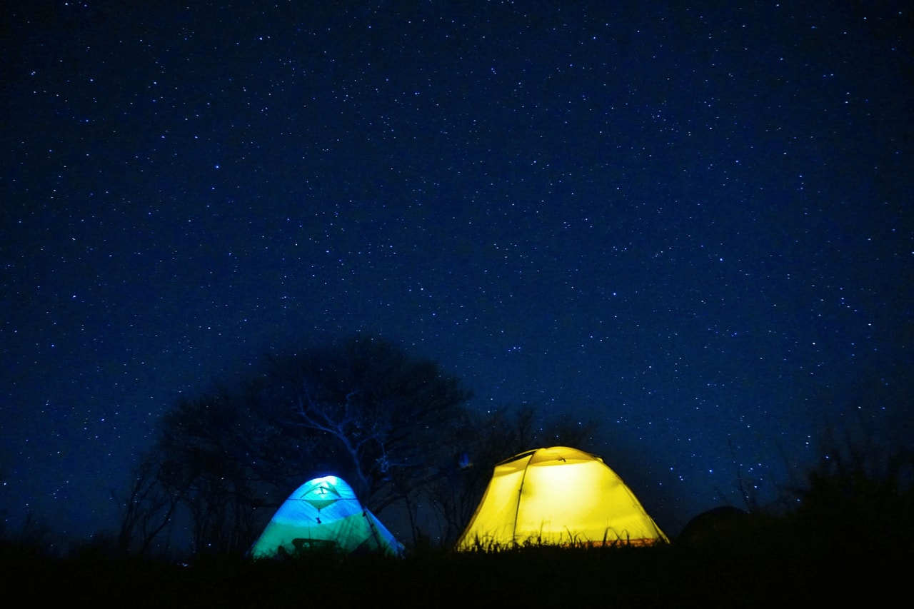A blue and yellow tent with lamps inside against a dark night sky