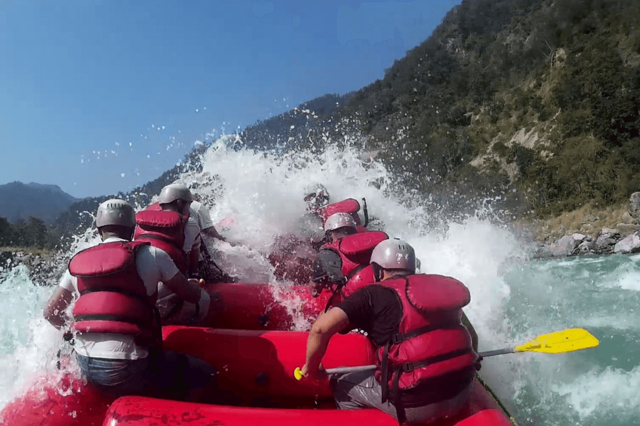 Group of rafters in life jackets getting splashed by water