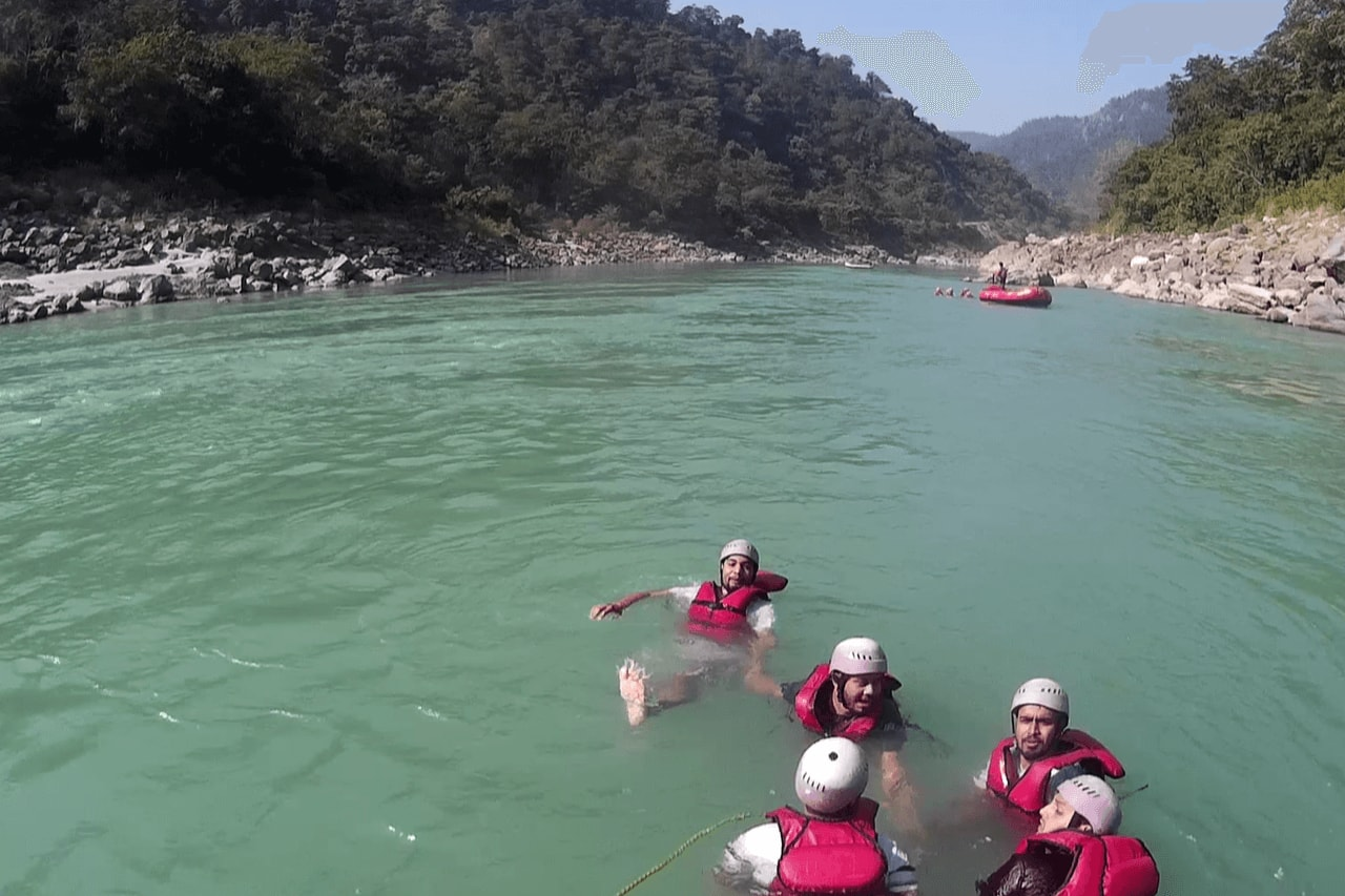 Swimmers with life jackets and helments swimming in river