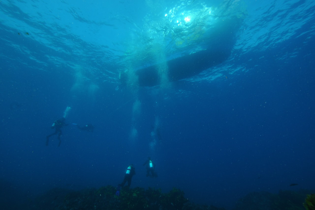 Three scuba divers descend from boat in blue ocean.