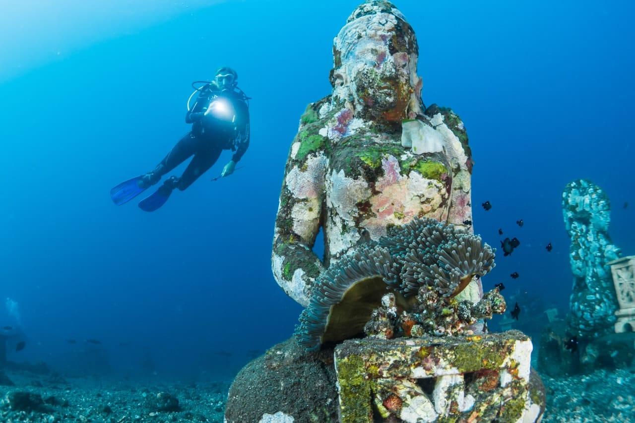 Scuba diver swims over algae-covered statue