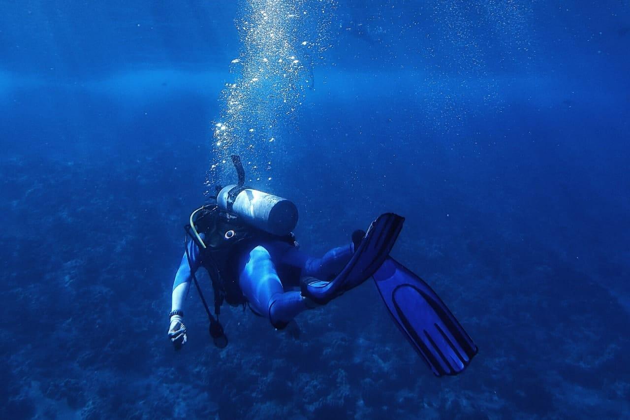 Scuba diver swims through blue ocean
