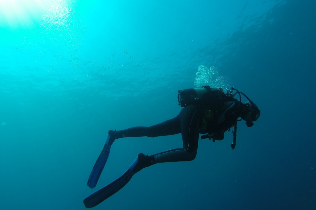 Shot from below of scuba diver ascending to surface.
