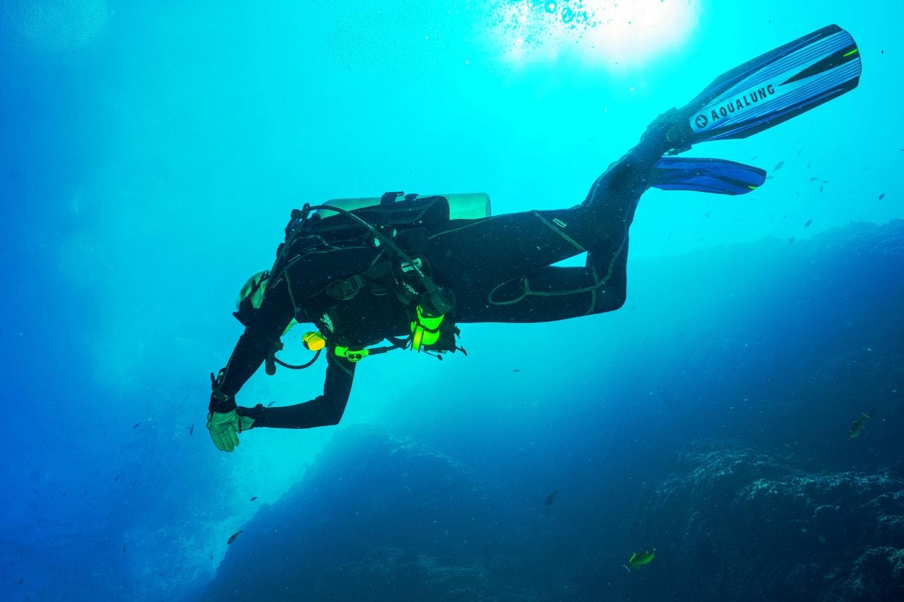 Three scuba divers descend from boat in blue ocean