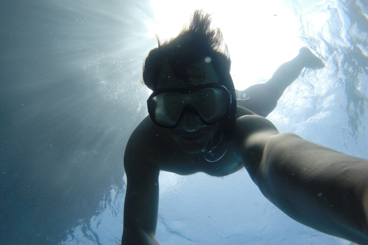 Snorkeller holds camera and takes his own photo underwater