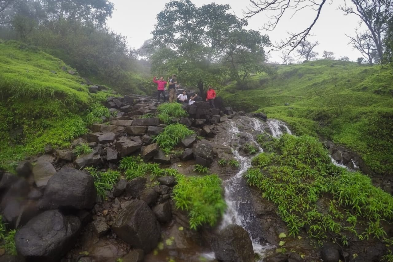 Trekkers stand atop a waterfall on a rainy day.