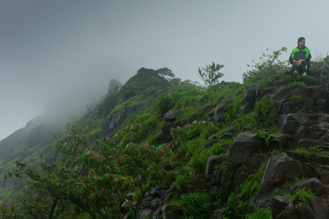 A solo trekker sits at the top of a hill on a rainy day