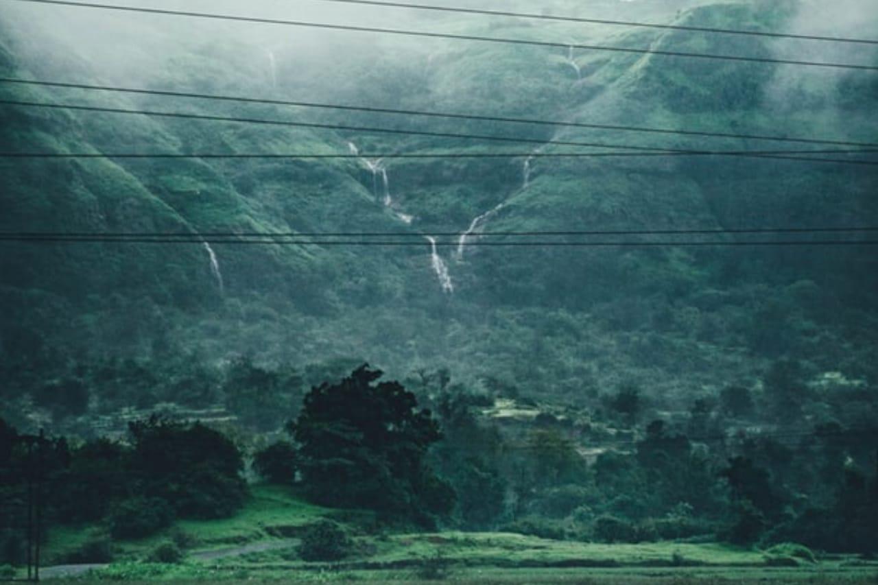 Waterfalls tumble down a massive green hill