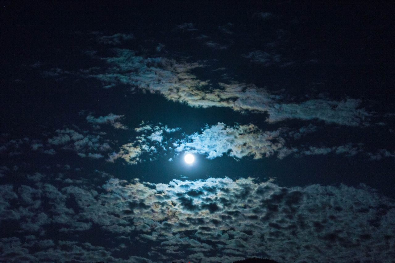 A full moon shines through the clouds at night